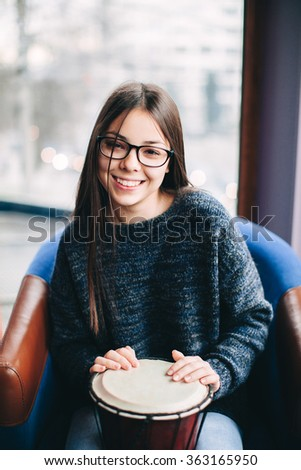 Smiling teenager girl playing african drum indoors - stock photo