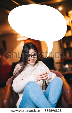 smiling teenager girl texting on her mobile phone with white blank text bubble - stock photo