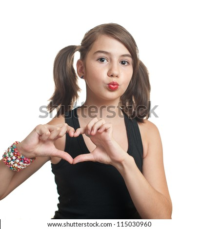 Smiling teenager girl with pigtails making heart shape with her hands isolated on white