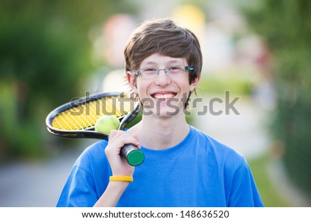 Smiling teenager holding a tennis racket in a suburban setting. - stock photo