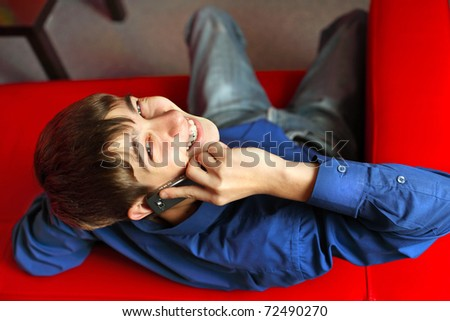smiling teenager in the room with mobile phone - stock photo