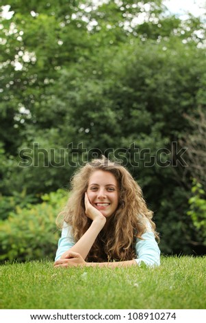 Smiling teenager lying on a grass in a park