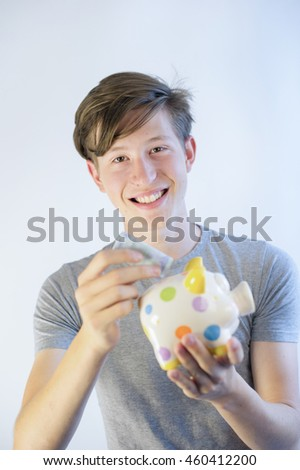 Smiling teenager putting euro bill into piggy bank.