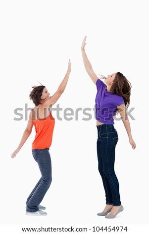 Smiling teenager standing on the tips of her toes while her friend is trying to touch her hand - stock photo
