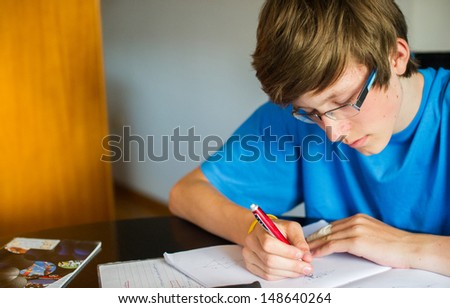Smiling teenager studying and doing his homework while holding his pen and writing in his notebook.