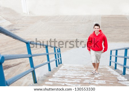 Smiling Teenager  walking from the boardwalk up stairs - stock photo