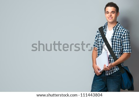Smiling teenager with a schoolbag standing on wall background - stock photo