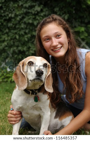 Smiling teenager with her old beagle dog