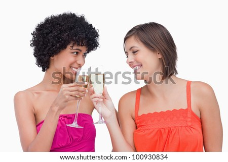 Smiling teenagers clinking glasses of champagne - stock photo
