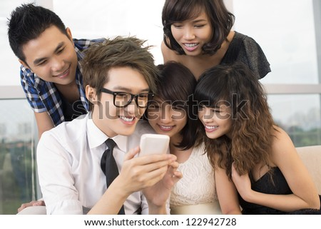 Smiling teenagers communicating via smart phone - stock photo