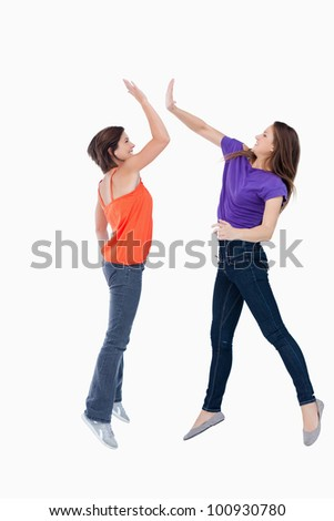 Smiling teenagers jumping while trying to high-five each other in the air - stock photo
