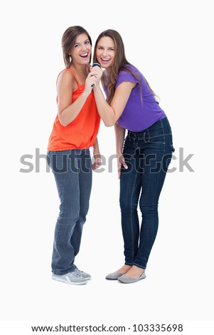 Smiling teenagers singing in a cordless microphone - stock photo