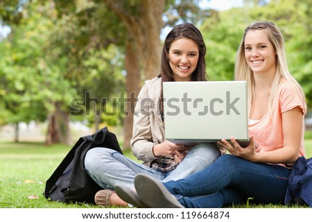 Smiling teenagers sitting while using a laptop in a park - stock photo