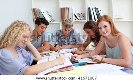 Smiling teenagers studying in the library. Concept of education