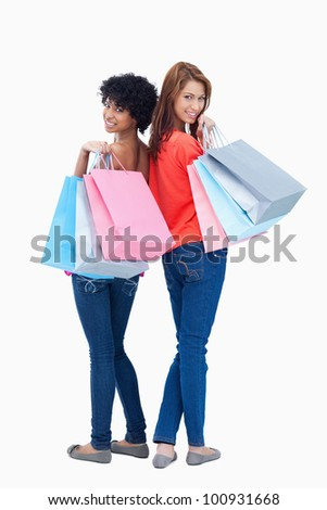 Smiling teenagers turning back their heads and holding shopping bags - stock photo