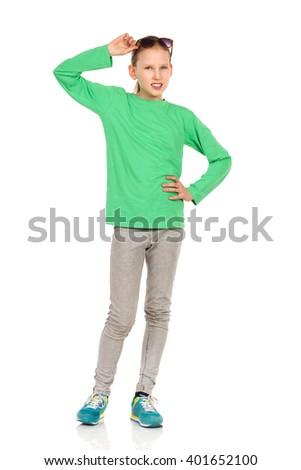 Smiling ten years old girl in green blouse, jeans and sneakers, posing with hand on hip, holding sunglasses on her head and looking at camera. Full length studio shot isolated on white. - stock photo