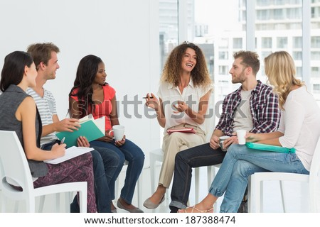 Smiling therapist speaking to a rehab group at therapy session - stock photo