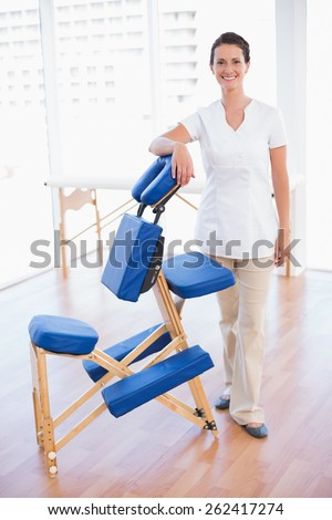 Smiling therapist standing with massage chair in medical office