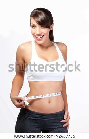 Smiling thin woman measuring waist