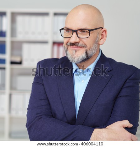 Smiling thoughtful businessman wearing glasses standing with folded arms staring off to the side into the distance - stock photo