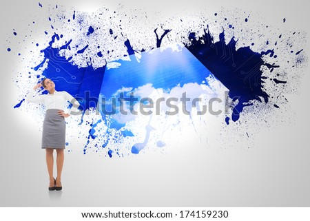 Smiling thoughtful businesswoman against splash on wall revealing cloud computing graphic