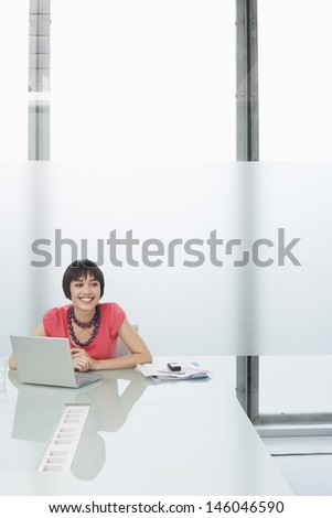 Smiling thoughtful young woman sitting with laptop in modern cubicle at office - stock photo