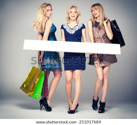 Smiling three beautiful blonde girls shopping, posing with empty boards. Studio shot. - stock photo