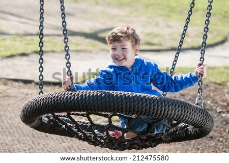 Smiling Toddler Boy on a Swing in the Park - stock photo
