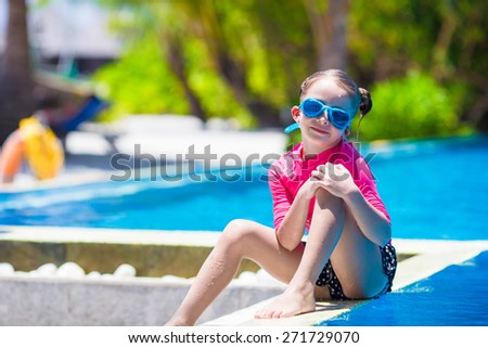 Smiling toddler girl having fun in outdoor swimming pool - stock photo