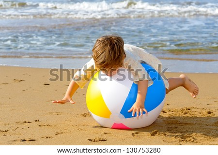 Smiling toddler girl playing with her inflatable ball at beach