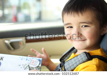 Smiling toddler inside a car.