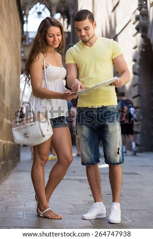 Smiling tourists couple in shorts reading the map at street - stock photo