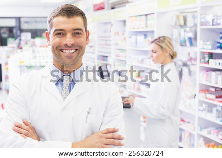 Smiling tpharmacist standing with arms crossed in the pharmacy
