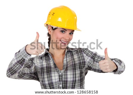 Smiling tradeswoman giving two thumb's up - stock photo