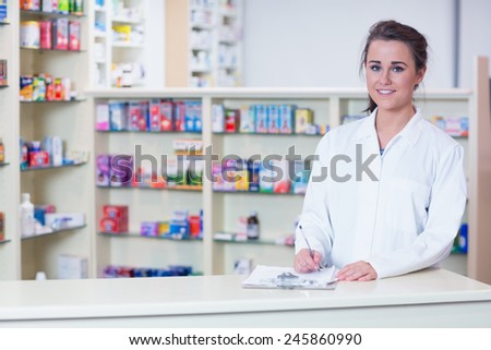 Smiling trainee in lab coat writing a prescription in the pharmacy - stock photo