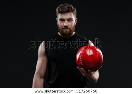 Smiling trainer with ball in hand. front view. isolated dark background