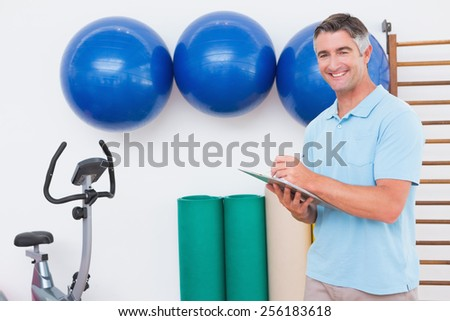 Smiling trainer writing on clipboard in fitness studio - stock photo