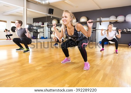 Smiling training group doing squat exercises at fitness gym - stock photo