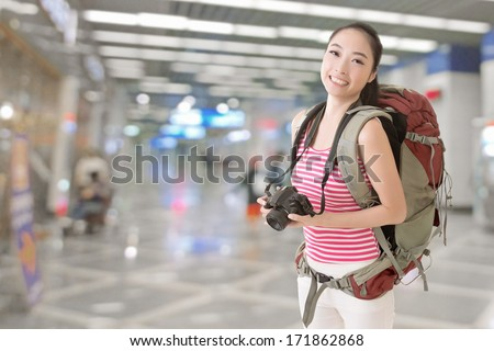 Smiling traveling Asian girl holding a camera and looking at you in the modern airport or train station. - stock photo