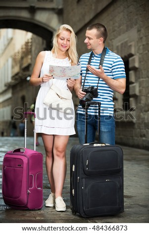 Smiling traveling couple searching for direction using paper map in town