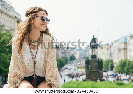 Smiling trendy hippie brunette woman tourist relaxing on stone parapet on Wenceslas Square in Prague. In the background Saint Wenceslas statue in Prague. Tourism travel concept. - stock photo