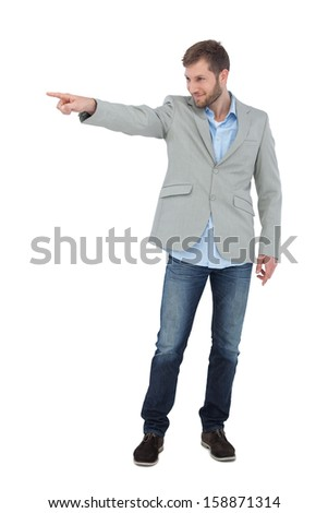 Smiling trendy model pointing to something on white background