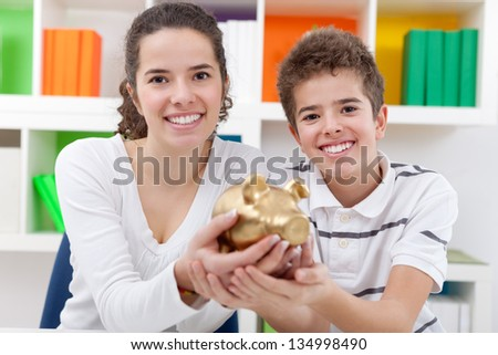 Smiling two children holding  piggy bank - stock photo