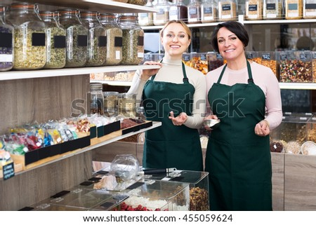 Smiling two female sellers wearing apron and standing next to organic foods in the bio-store