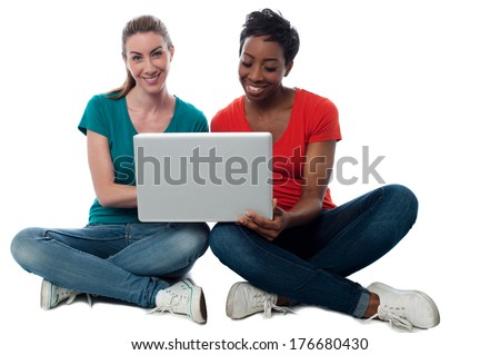 Smiling two friends watching videos on laptop - stock photo