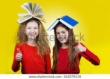 Smiling  Two sisters , little schoolgirl  with thumb up and books on their head, isolated over yellow background.  - stock photo