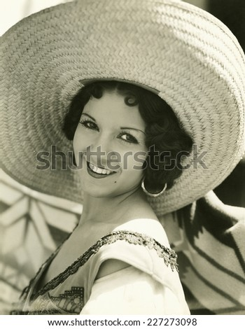 Smiling under her straw hat - stock photo