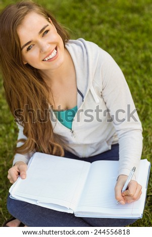 Smiling university student sitting and writing on notepad in park at school - stock photo