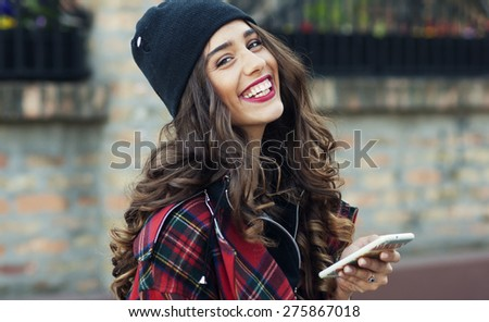 Smiling urban girl uses smart phone with smile on her face - stock photo