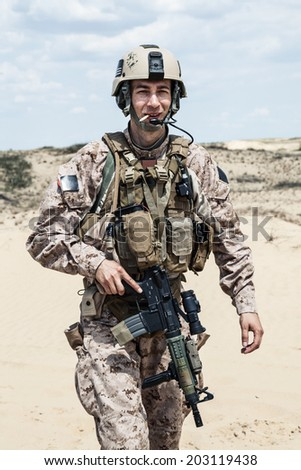 smiling US marine in the desert smoking a cigarette - stock photo